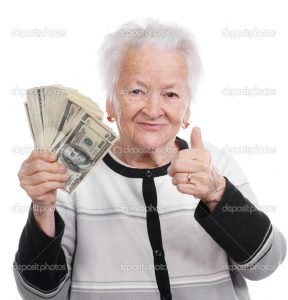 Portrait of an old woman holding money in hand and showing yes sign on white background